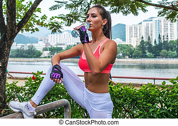 Sporty young female athlete taking a break after exercising or running, standing and drinking water from  bottle in park on summer day with river  city buildings behind her back