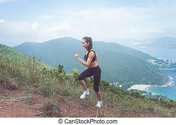 Fit female jogger exercising, running uphill with sea and...