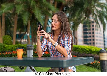 Young woman sitting at a table outdoors using her mobile...