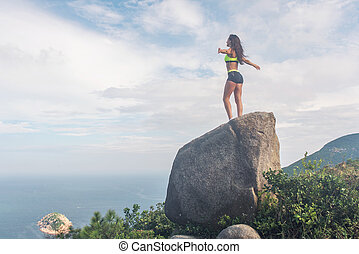 Rear view of inspired sportswoman standing on a rock in the...