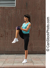 Young fitness woman doing warm-up exercise before running...