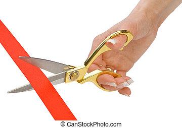Scissors in a female hand cut a red tape