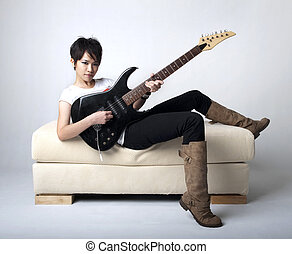 Punk Rockstar holding a guitar sitting on sofa