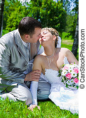 The wedding pair sits on a grass kiss