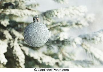 Silver Christmas balls hanging on a branch of fir tree