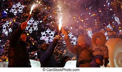 The family holds the firework outdoors in the winter. In the background, lights and garlands of Christmas fir