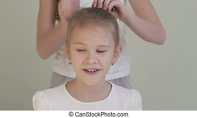 One girl  combing his sister at home