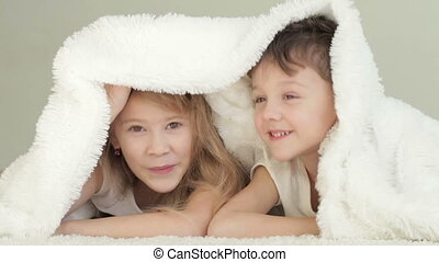 Lovely children lying in bed at home. Concept of Brother And...