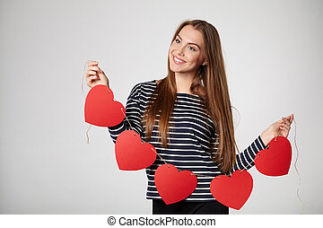 Smiling woman holding garland of five red paper hearts -...