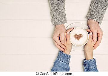 Couple holding hands with coffee on white table, top view