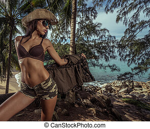 Beautiful brunette woman with straw hat and sunglasses in...