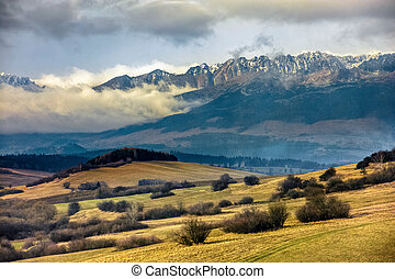 snowy peaks of Tatra mountains in evening haze behind the...