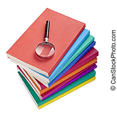 close up of colorful books and magnifying glass on white...