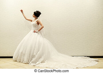 The gordeous bride stands in the room