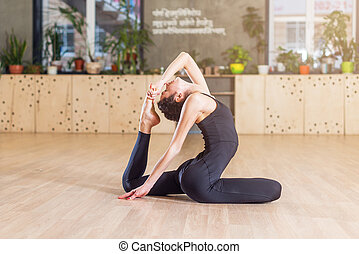 Woman working-out in studio doing stretching exercise...