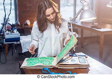 Pretty female tailor choosing a fabric in cloths catalog in...