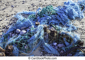 Plastic pollution - blue tangled fishing nets washed up on the beach