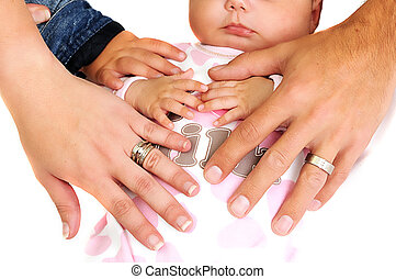 family placing hands on new baby girl with wedding rings...