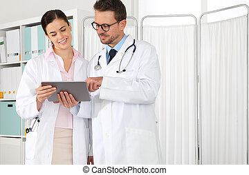 Doctor use the tablet, with intern, concept of medical consulting