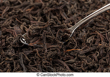 Black tea in a spoon on a black tea background. Close-up...