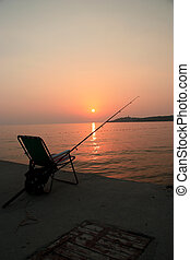 fishing in the sunset - a fishing rod and a deck chair left...