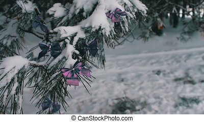 Decorated snowy forest tree with lilac ribbons - Decorations...