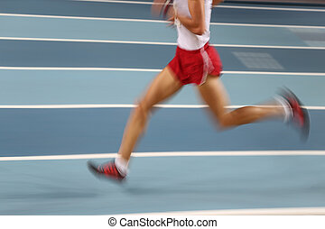 Blured athletes running in track and field