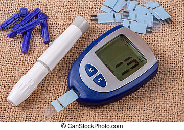 The blood glucose meter on the background of burlap