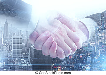 handshake - Close up of handshake on city background. Double...