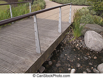 wooden bridge over pebbly pond