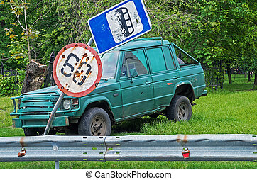 Accident - Damaged road signs on background old broken car