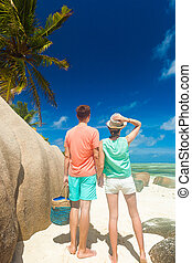 young couple relaxing at beach with granite rocks. Anse...