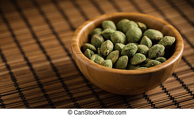 wasabi peanuts - wooden bowl filled with wasabi covered...