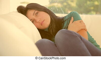 Beautiful woman slowly falling asleep on sofa tired thinking...