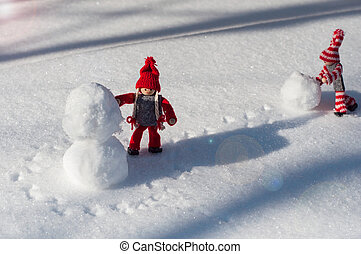 Two toy little man rolled a snowball - building a snowman...
