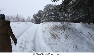A girl in a long brown coat walks on a snow-covered forest...