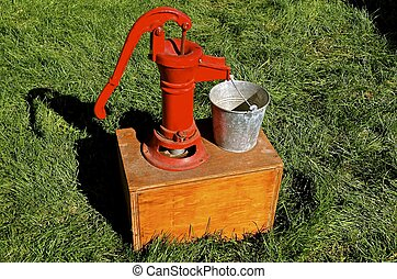 Red restored hand pump - A mounted hand pump on a box with...