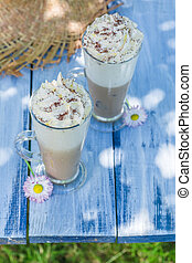 Sweet coffee with cream in sunny day