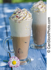 Sweet latte with cream in sunny day