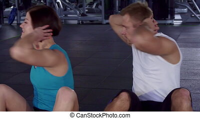 Fitness man and woman train their abdominal muscles -...