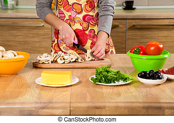 Closeup of girl hands cutting the mushrooms in the kitchen -...