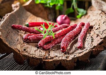Homemade small thin kabanos sausages on bark