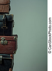 Background stack of old shabby suitcases form a tower....
