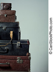 Background stack of old shabby suitcases and camera. Concept...