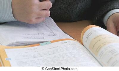 Schoolboy sitting at the desk making home task