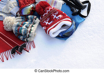 Winter sports background with ski poles, goggles, hats and...