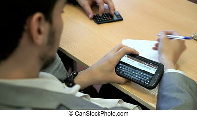The student sitting at a desk holds a cellphone - The...