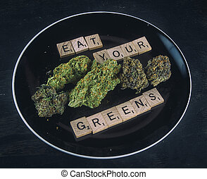 Plate with cannabis buds on black - infused medical...