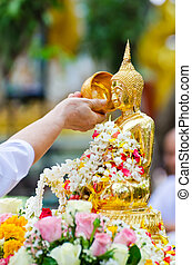 people showering buddha statue on Songkran festival in...