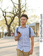 Hispanic student with curly hair walks on tree lined campus....